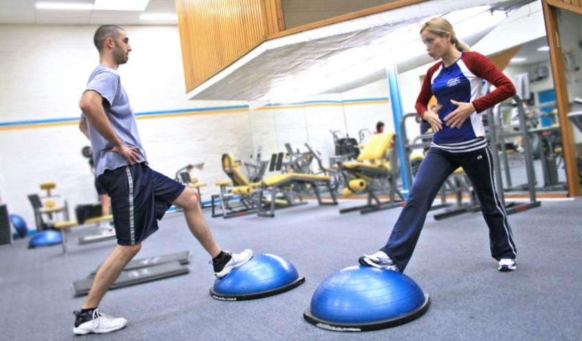 A Female Personal Trianer Helping A Man Workout In A Gym