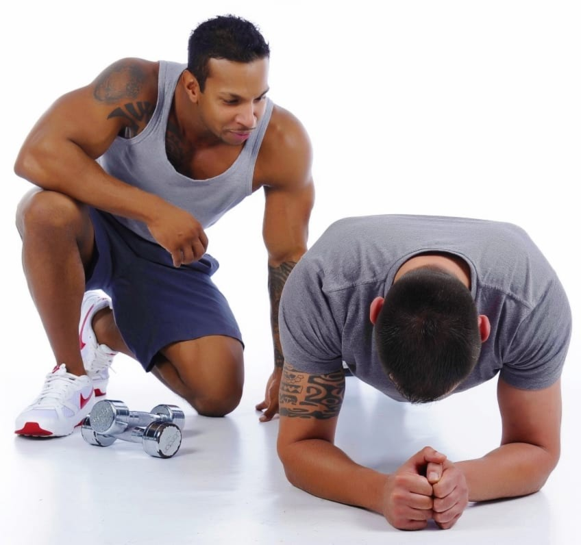 Personal Trainer Helping A Man Do A Plank